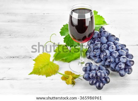 Glass red wine with cluster grapes on wooden board - stock photo