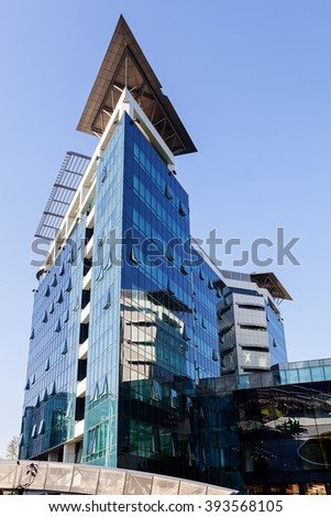 Glass reflective office building against blue sky on a sunny day - stock photo