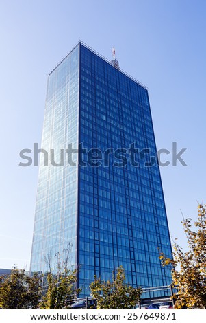 Glass reflective office building skyscraper against blue sky on a sunny day - stock photo