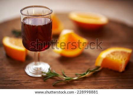glass ruby sweet wine and oranges on wooden background. shallow doff