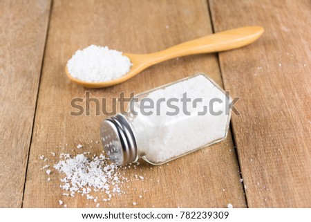 glass salt shaker on wooden and salt on wooden spoon