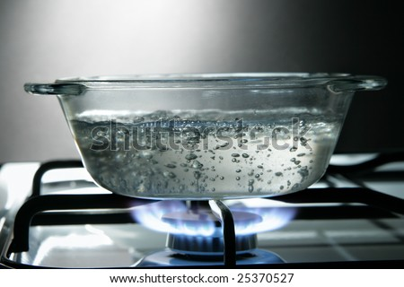 Glass saucepan on the gas stove close-up - stock photo