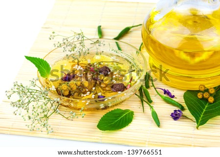 Glass saucer and carafe with oil and herbage with green leaves on the mat - stock photo