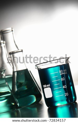 Glass scientific beaker filled with blue chemical liquid and laboratory conical Erlenmeyer flasks for a chemistry experiment in a science research lab - stock photo