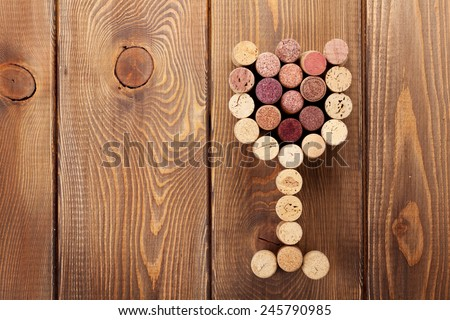 Glass shaped wine corks over rustic wooden table background. View from above with copy space - stock photo