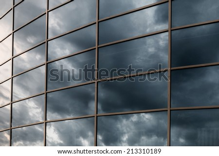 Glass skyscraper wall with reflection of dark stormy clouds at sunset. - stock photo