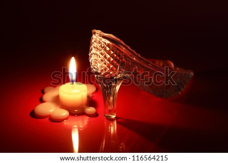 Glass slipper near lighting candle on black and red background - stock photo