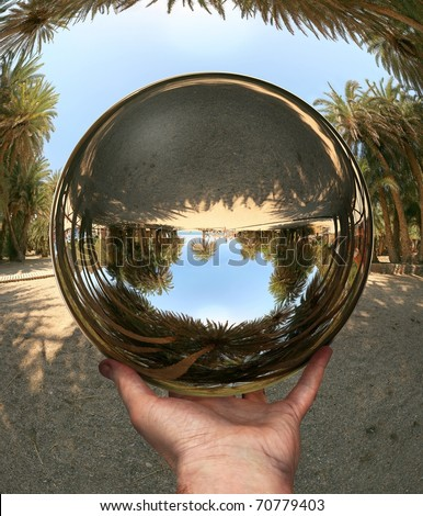 Glass sphere in hand, photocollage (a lot of my shots as a source). Vai Beach. Crete. - stock photo