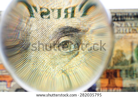 Glass sphere on a banknote of 100 US dollars. The increased image of an eye of Benjamin Franklin and the word Trust against a blurred background of 100 US dollars bill. - stock photo