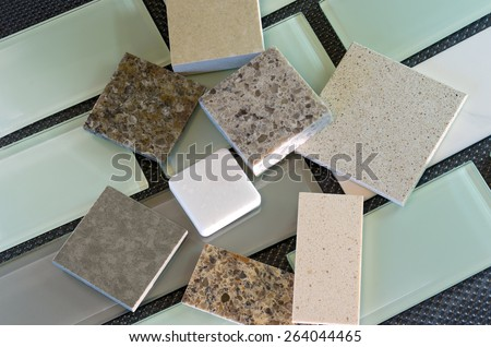 Glass subway tile samples used in kitchen backsplashes and quartz samples for countertops - stock photo