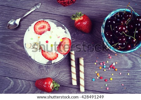 Glass sundae with tasty milk ice-cream with sauce, ripe strawberries and Crispy sweet stick on the wooden table and bowl with cherries. Sundae ice cream in cup, top view - stock photo