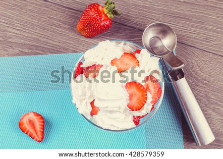 Glass sundae with tasty milk ice-cream with sauce, ripe strawberries on the blue napkin. Sundae ice cream in cup, ice cream spoon on the wooden table, top view - stock photo