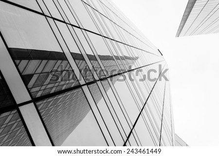 Glass surface of skyscrapers view in district of business centers with reflection on it, black and white  - stock photo