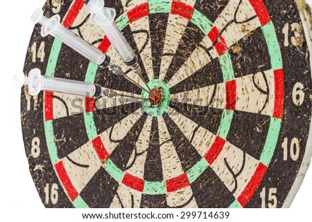 Glass syringe and needle as darts arrows in the target center bulls eye - stock photo