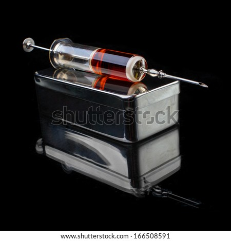 Glass syringe with stainless steel box on a black background. - stock photo