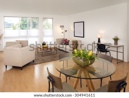 Glass table in modern loft with sofa, couch and chairs. - stock photo
