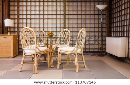 Glass table with wickler chairs in an elegant interior
