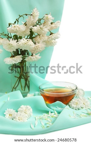 Glass tea cup and flowers on satin background