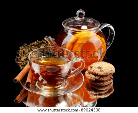 Glass teapot and cup with black fruit tea and cookies isolated on white - stock photo