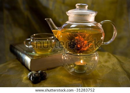 Glass teapot and cup with green tea - stock photo