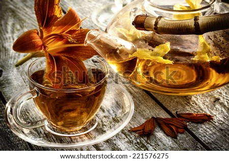 Glass teapot and cup with  lily flower on old wooden table. - stock photo