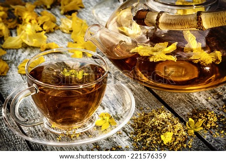 Glass teapot and cup with osmanthus flower on old wooden table. - stock photo
