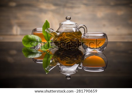 Glass teapot and small tea bowl with green tea - stock photo