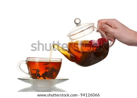 Glass teapot pouring black tea into cup isolated on white - stock photo