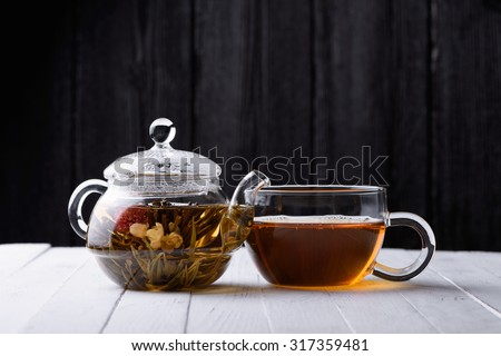 Glass teapot with blooming green tea and cup of tea on white wooden table and dark background still life - stock photo