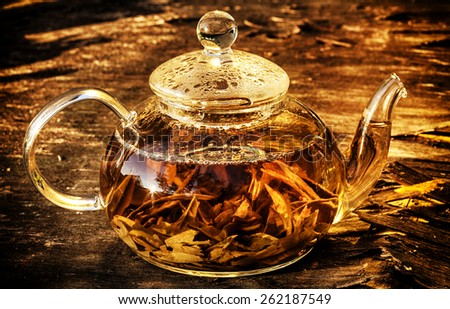 Glass teapot with green tea on old wooden table. - stock photo