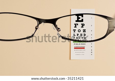 glass  testing  on eye exam chart - stock photo
