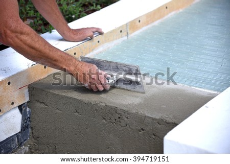 Glass tile layer is working on an outdoor fountain, water feature. - stock photo