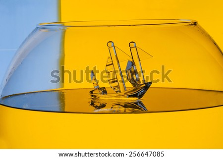 glass toy ship in water on color background - stock photo