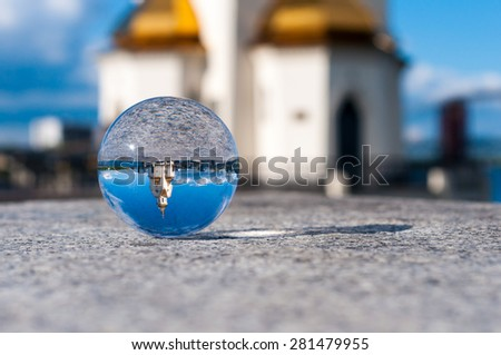 Glass transparent ball on church background and grainy surface. Texture, outdoors - stock photo