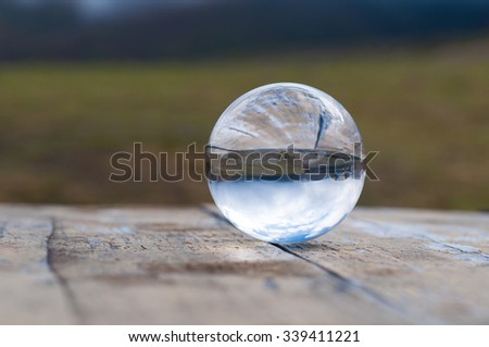 Glass transparent ball on dark green background and wooden surface. Soft focus. With empty space for text. - stock photo