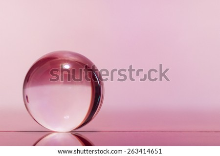 Glass transparent ball on pink background and mirror surface. Texture - stock photo