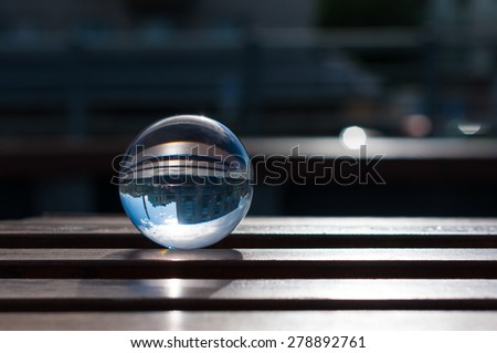 Glass transparent ball on wooden slats background. With empty space. Texture, outdoors - stock photo