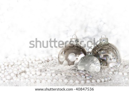 Glass transparent christmas balls and pearls against a white background; making a fresh xmas scene with plenty of copyspace - stock photo