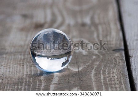 Glass transparent crystal glass ball on dark wooden background. Soft focus. With empty space for text - stock photo