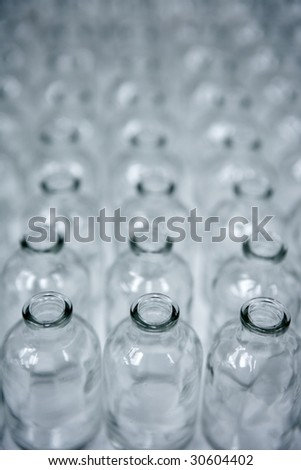 Glass transparent empty bottles in rows, cosmetics assembly line - stock photo
