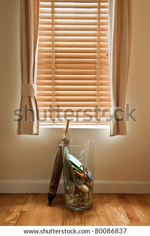 Glass transparent vase with shells, maps and slingshot with traditional Thai umbrella at the window - stock photo