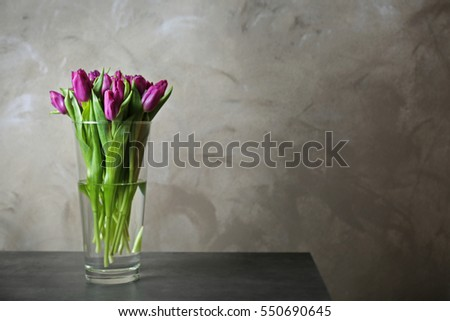 Glass vase with bouquet blur of beautiful tulips on color background