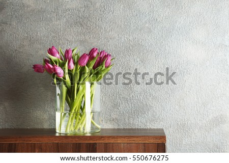 Glass vase with bouquet of beautiful tulips on color background