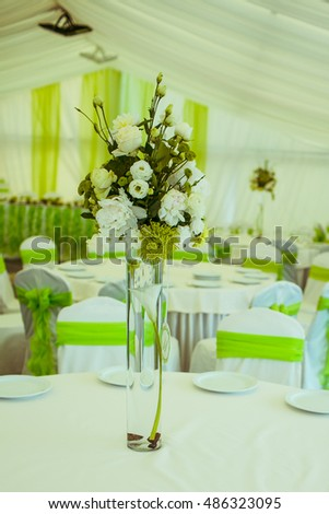 Glass vase with green bouquet stands on the round white table