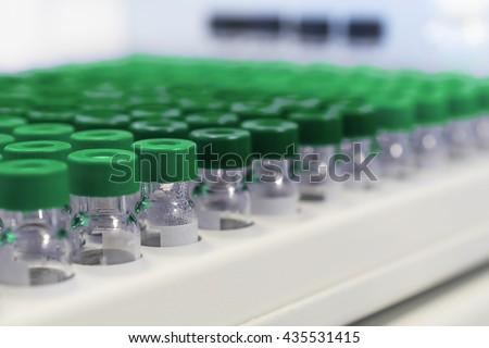 Glass vials in the tray automatic liquid dispenser. - stock photo