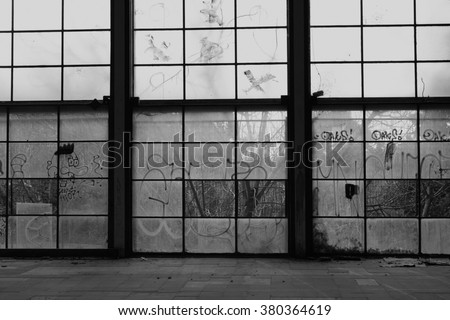 Glass wall broken windows in abandoned gym interior. Black and white. - stock photo