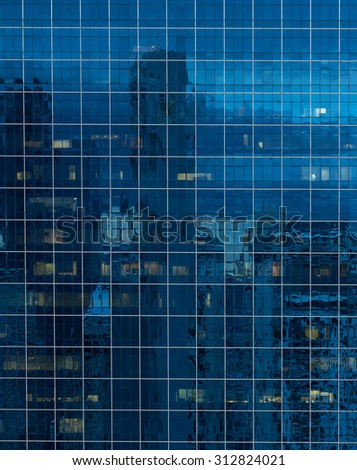 glass wall of a office building reflect view of city with skyscraper - stock photo