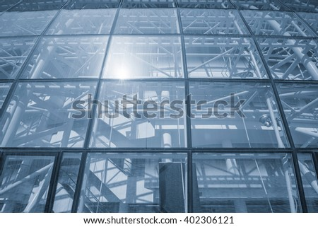 Glass wall of the modern building with metal constructions inside. - stock photo