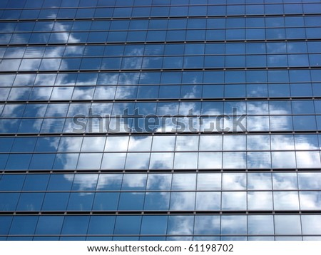 Glass wall with the reflection of blue sky and clouds - stock photo