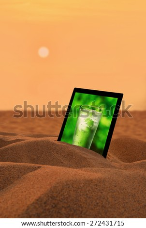 Glass water in the tablet PC on the desert Precious water image,Concept for growing business, ecology, freshness, freedom and other lifestyle issues.  - stock photo
